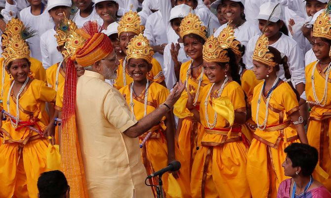Indian Prime Minister Modi greets school girls dressed as Hindu Lord Krishna, after addressing the nation from the historic Red Fort during Independence Day celebrations in Delhi